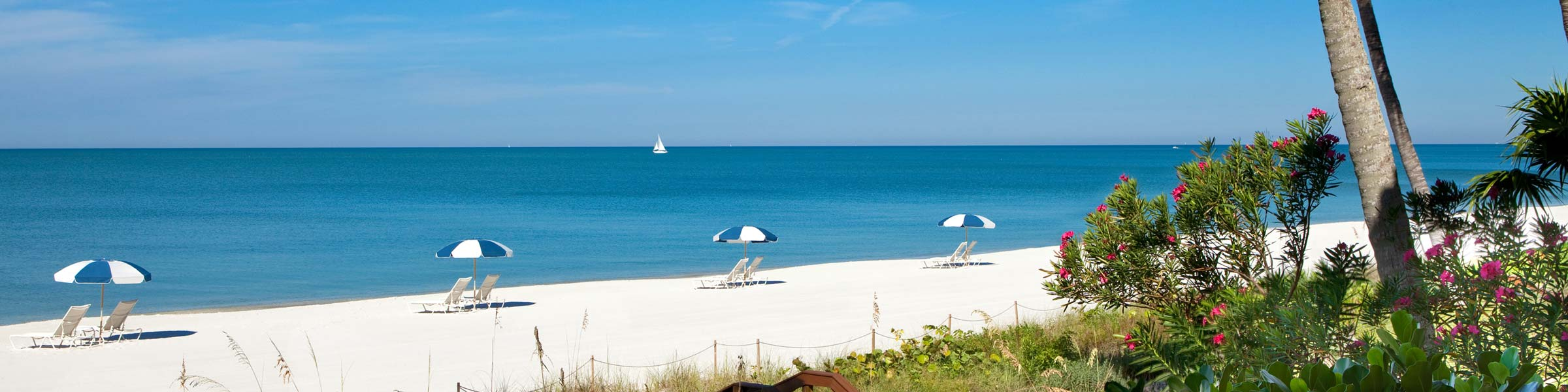 Beach view with lounge chairs and umbrellas in Naples, FL
