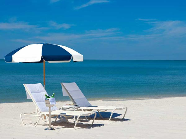 Lounge chairs, umbrella, and drinks at La Playa Beach and Golf Resort in Naples, FL