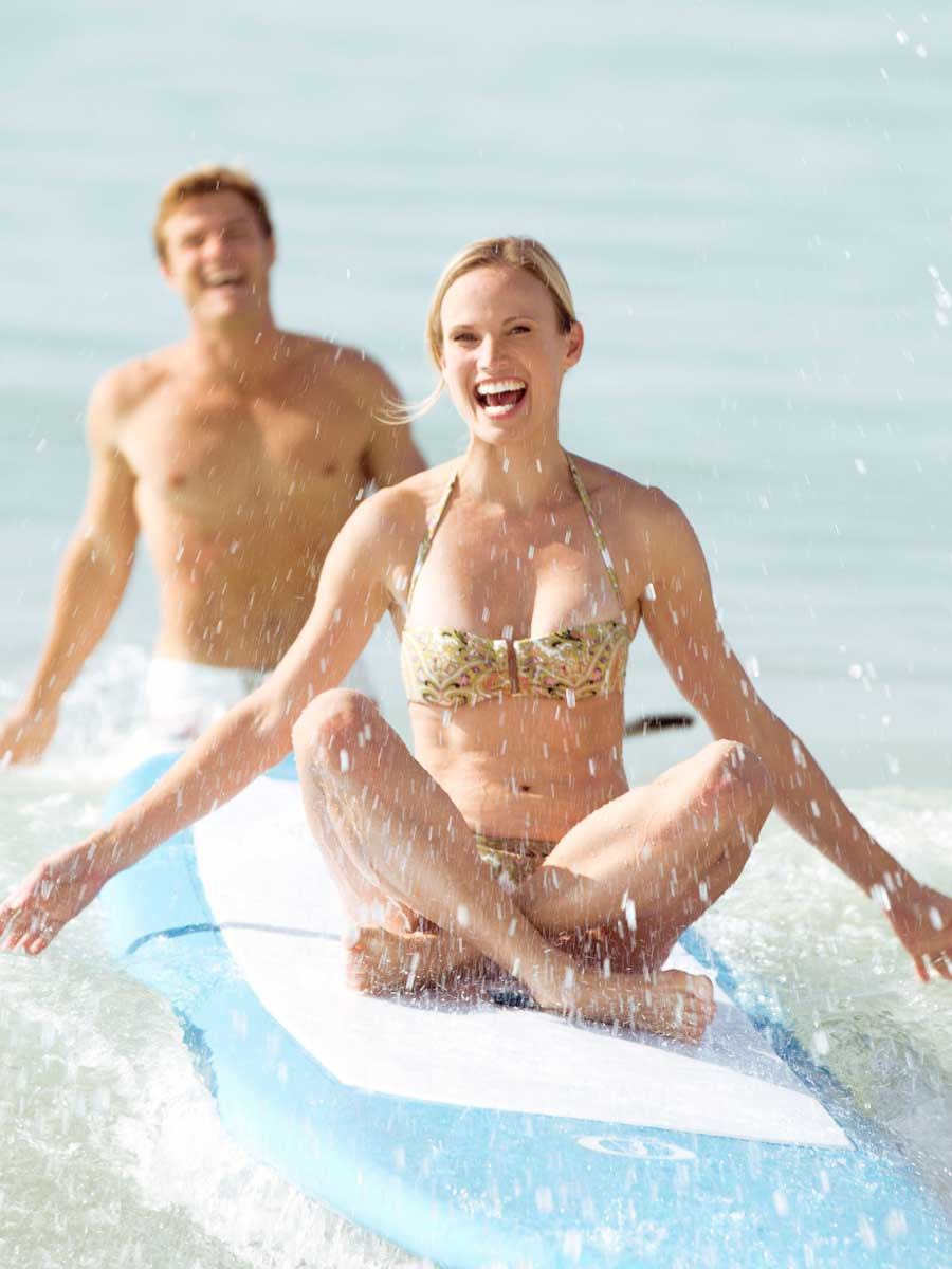 Couple on surfboard in Naples, FL
