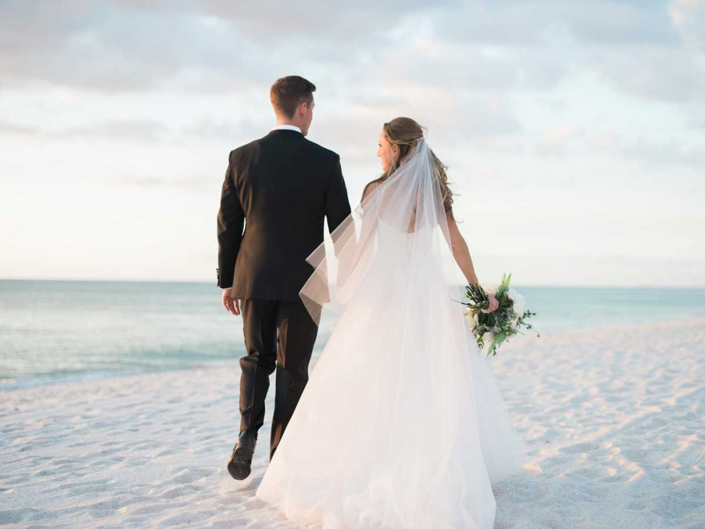 Newly weds holding hands on beach in Naples, Florida